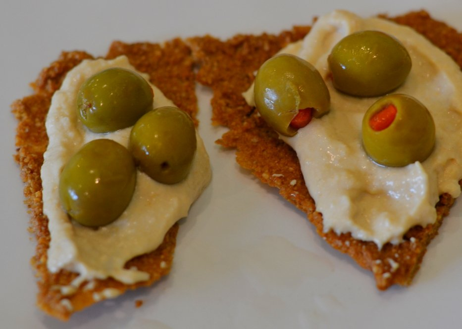 Raw crackers with hummus and olives