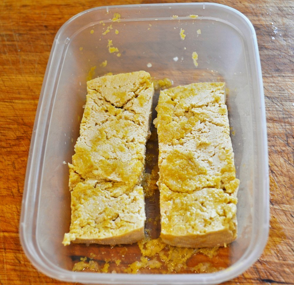 Tofu marinating in nutritional yeast, olive oil, salt and lemon juice