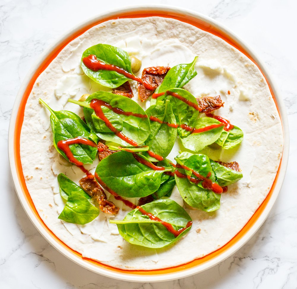 air fried wrap with cream cheese, sundried tomato, olives, spinach and sriracha