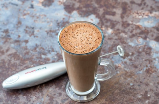 hot chocolate in a glass and a milk frother